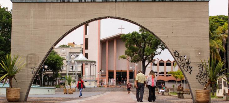 Praça Rui Barbosa, em Bauru, com a Igreja ao fundo e algumas pessoas transitando pela praça.